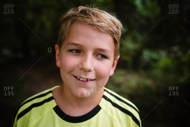 Smiling blonde boy outside in soccer jersey