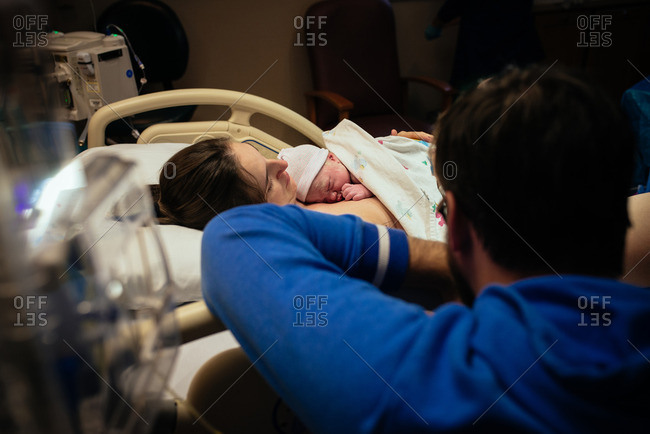 Dad watching newborn lying on mom