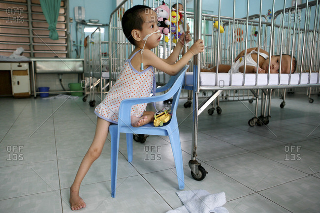 Ho Chi Minh City, Vietnam - March 11, 2009: Girl with a feeding tube in a chair beside a  child in crib