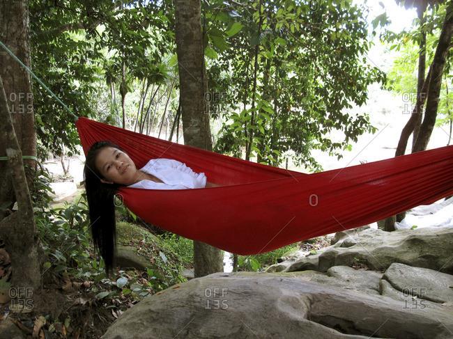 Vietnam - March 17, 2009: Woman lying in a hammock in a forest