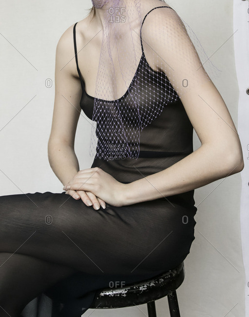 Woman in a black body suit sitting on a stool