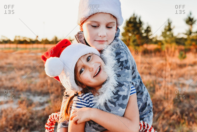 Kids hugging in field at Christmastime