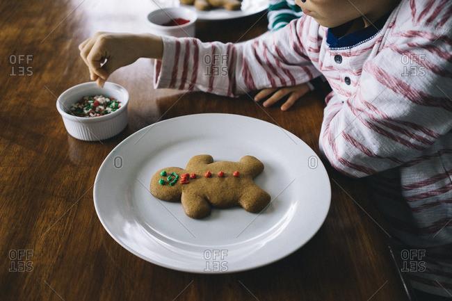 Boys decorating traditional Christmas cookies