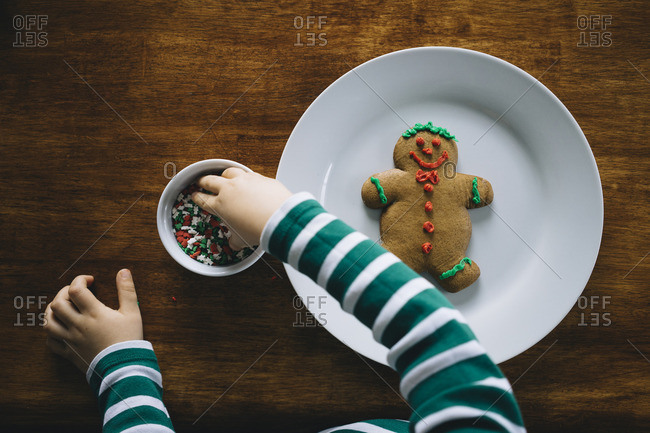 Hands of child decorating a Christmas cookie