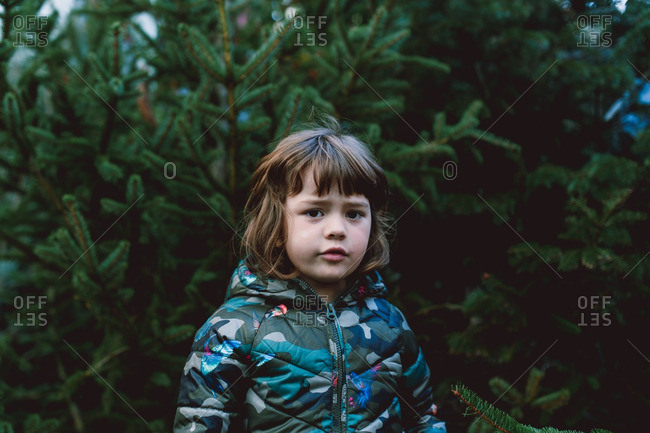 Girl in camouflage coat stands among pine trees