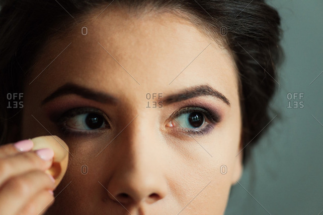 Woman applying foundation makeup to face