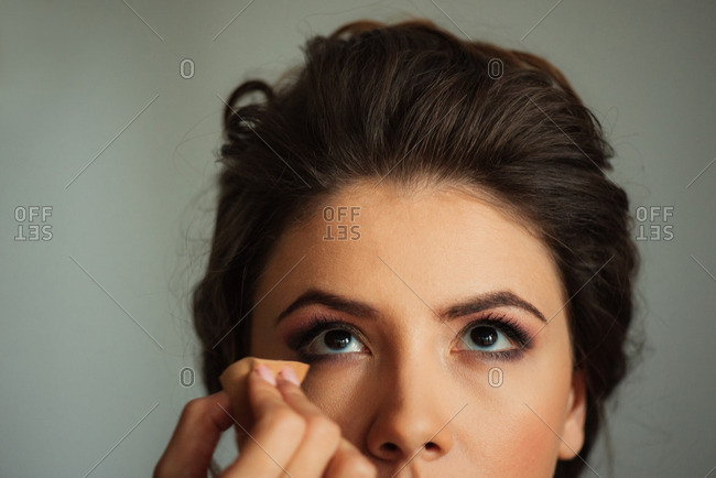 Woman looks up as makeup is applied underneath her eye