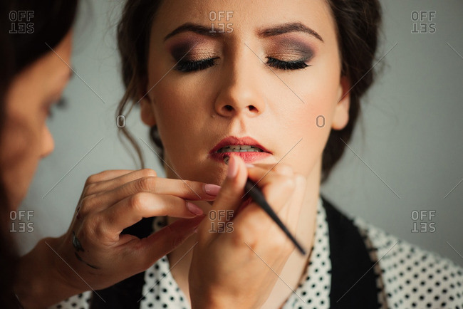 Woman closes eyes as makeup artist applies lip color with brush