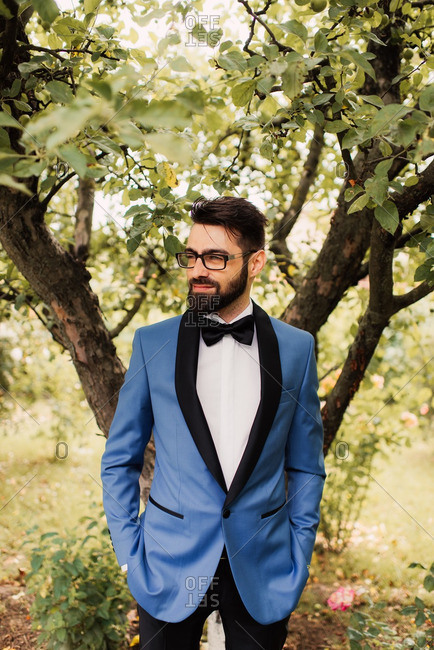 Groom in blue tuxedo jacket standing in front of tree