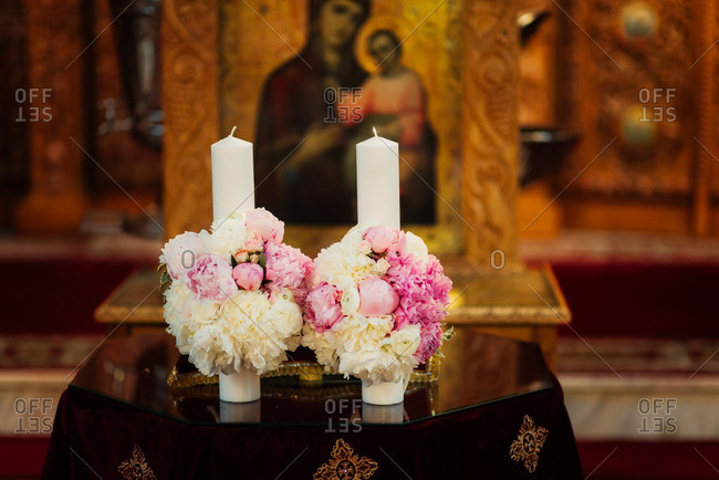 White candles with flowers on church altar