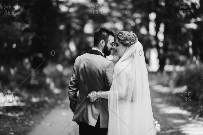 Groom and bride share romantic moment on forest road