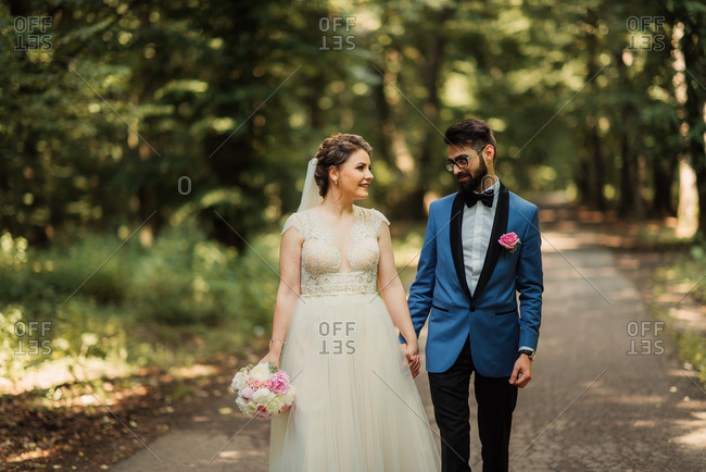 Groom gazes adoringly at bride as they walk in the woods