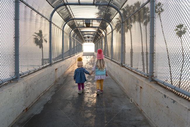 Sisters standing on beach overpass