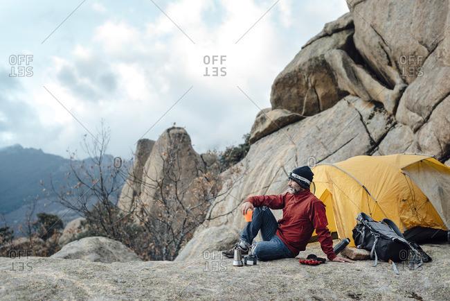 Man camping in rocky peaks
