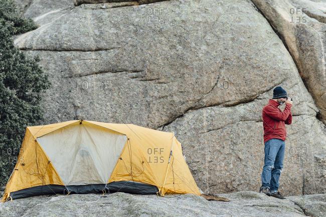 Man in remote campsite taking photo