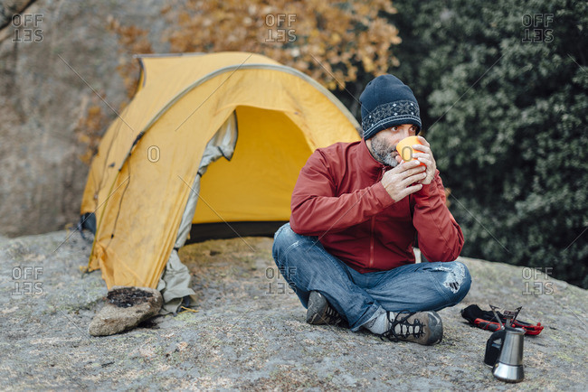 Man having drink in wilderness campsite
