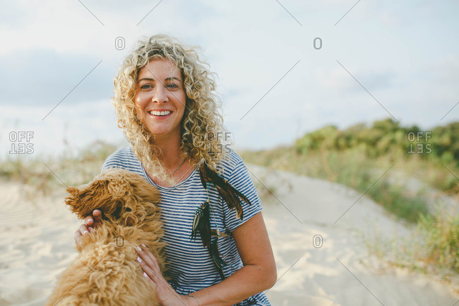 A woman with dog in sand dunes