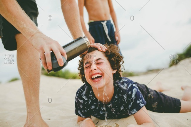 Boy getting face rinsed with water in sand