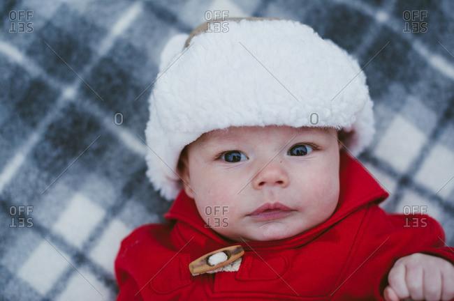 Portrait of baby in cap on plaid blanket