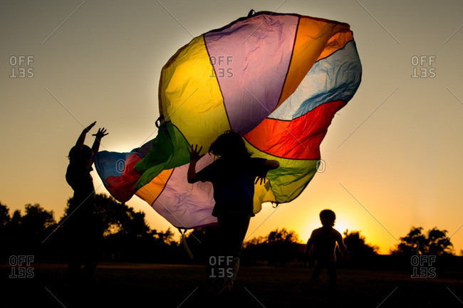 Children playing with a colorful parachute at sunset