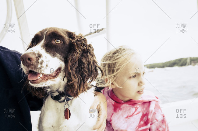 Woman hugging dog near daughter