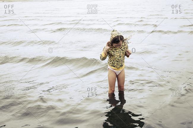 Girl wearing hoody wading in ocean