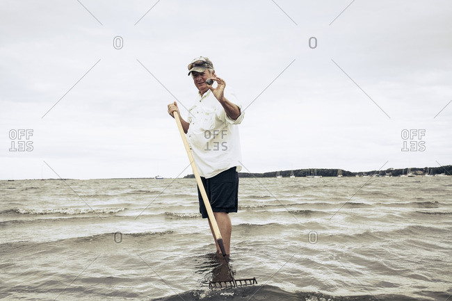 Man wading in ocean holding clam and rake