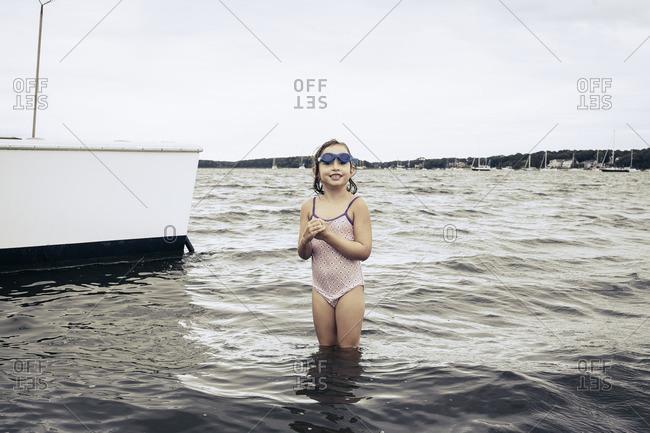 Smiling girl wading in ocean near boat