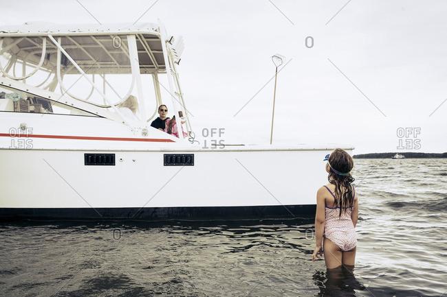 Girl wading in ocean talking to people in boat