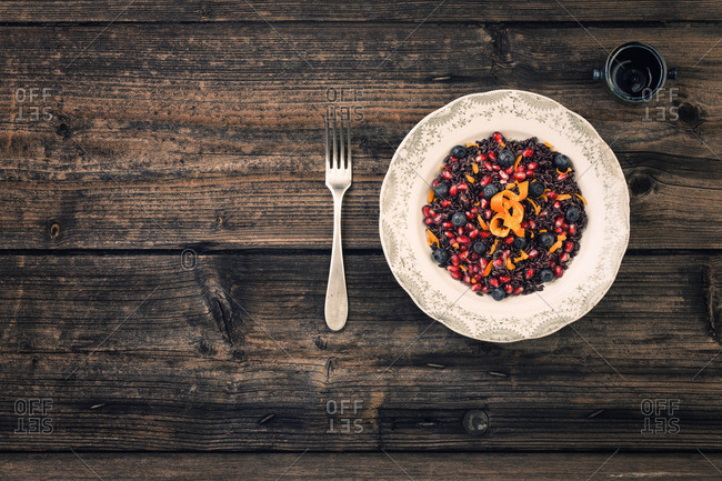 Bowl of black grains and berries on a rustic table