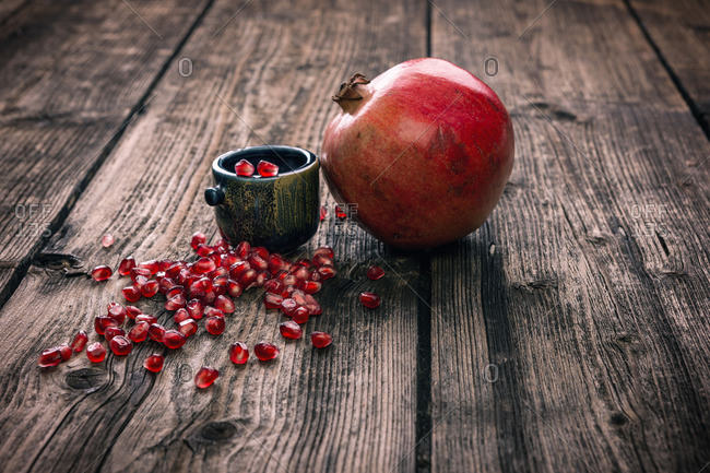 Whole pomegranate and seeds on a rustic table