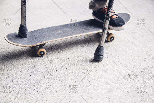 One-legged man riding skateboard with crutches