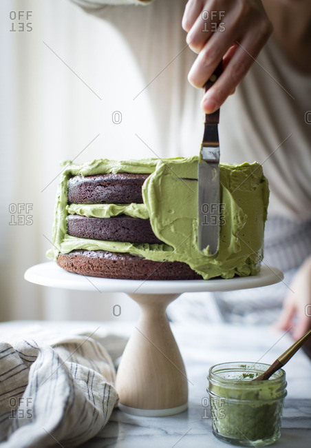 Woman frosting a chocolate zucchini layer cake with matcha cream cheese icing