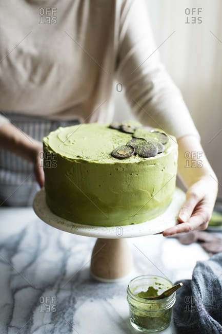 Woman placing a chocolate zucchini layer cake on a counter