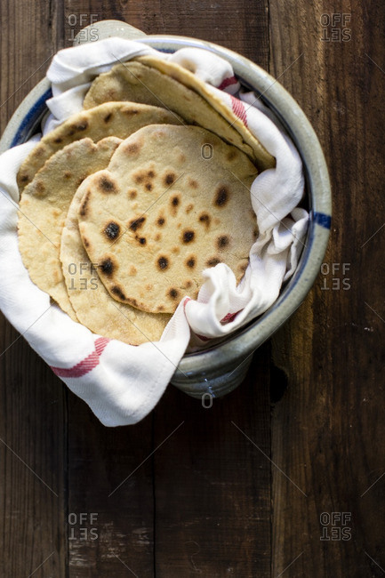 Homemade tortillas in a crock with cloth napkin
