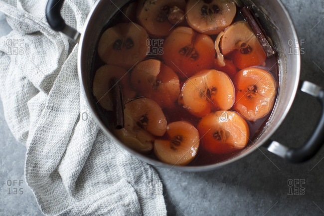 Poached quince and cinnamon sticks in a pot
