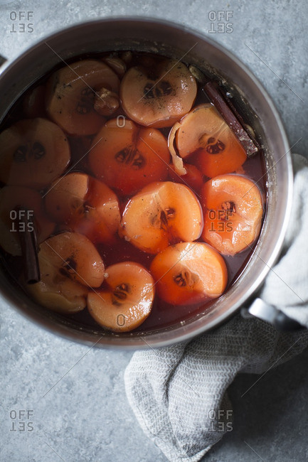 Quince, poaching liquid and cinnamon sticks in a pot
