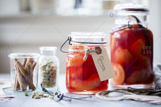 Poached quince fruit cinnamon sticks and cardamom in mason jars