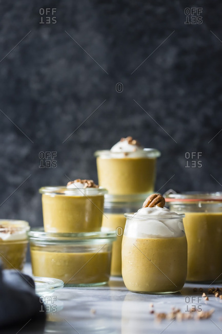 Various sized jars filled with pumpkin butterscotch pudding and whipped mascarpone