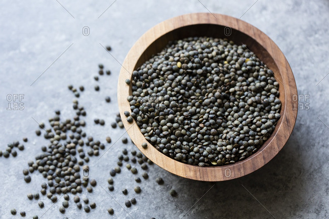 Uncooked black lentils in a wooden bowl