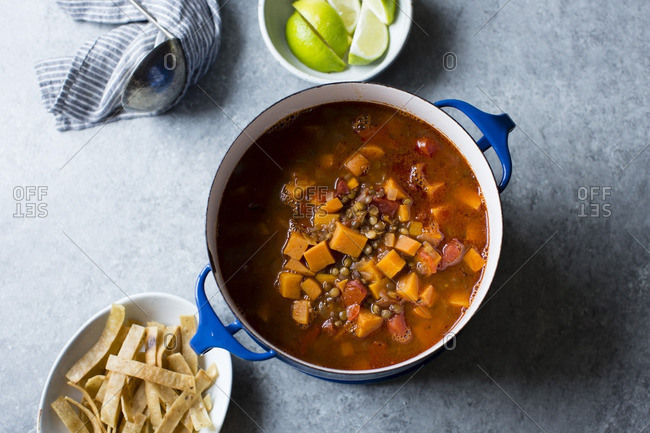Smoky sweet potato and lentil soup in a pot with tortilla strips and lime wedges