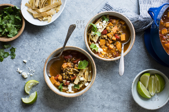 Bowls of smoky sweet potato and lentil tortilla soup with cilantro and lime