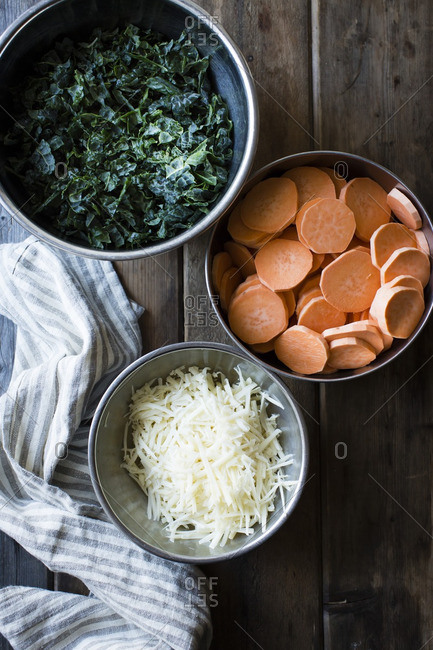 Mixing bowls of kale, sweet potato and white cheese