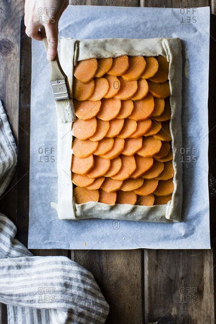 Woman brushing the pastry edges of a sweet potato galette