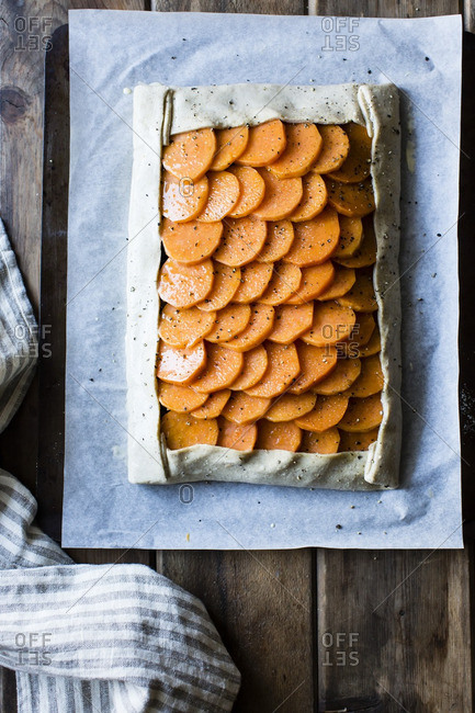 Uncooked sweet potato galette on parchment paper