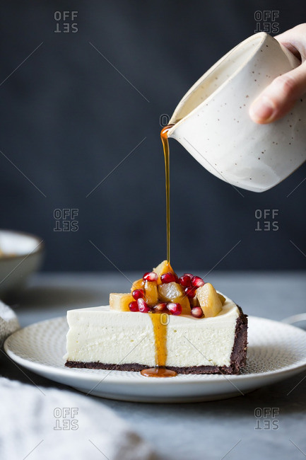 Woman pouring honey on a piece of chocolate crusted cheesecake