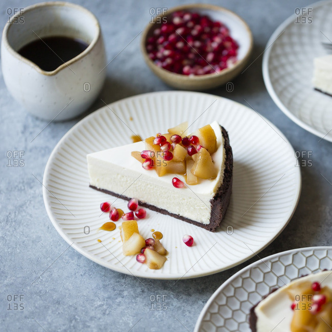 Piece of chocolate crusted cheesecake with honey, pears and pomegranate seeds