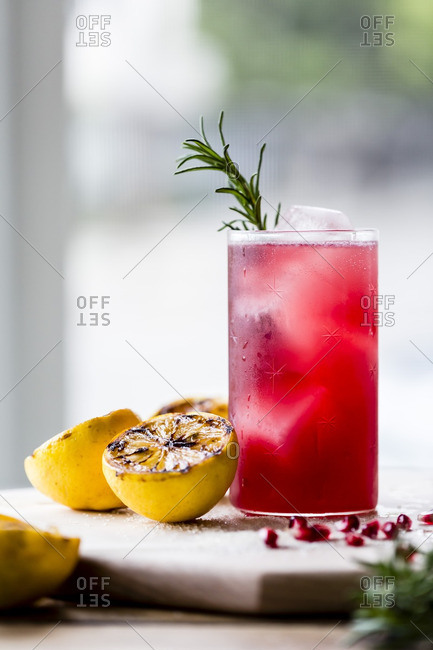 Pomegranate and rosemary cocktail with halved lemons