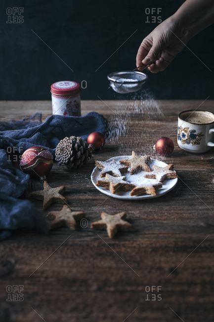 Woman dusting almond cinnamon Christmas cookies with powdered sugar