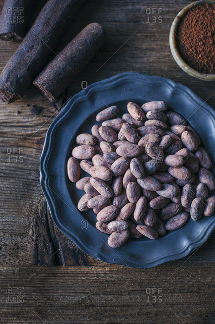 Raw cacao beans on a plate, with cacao sticks and powder